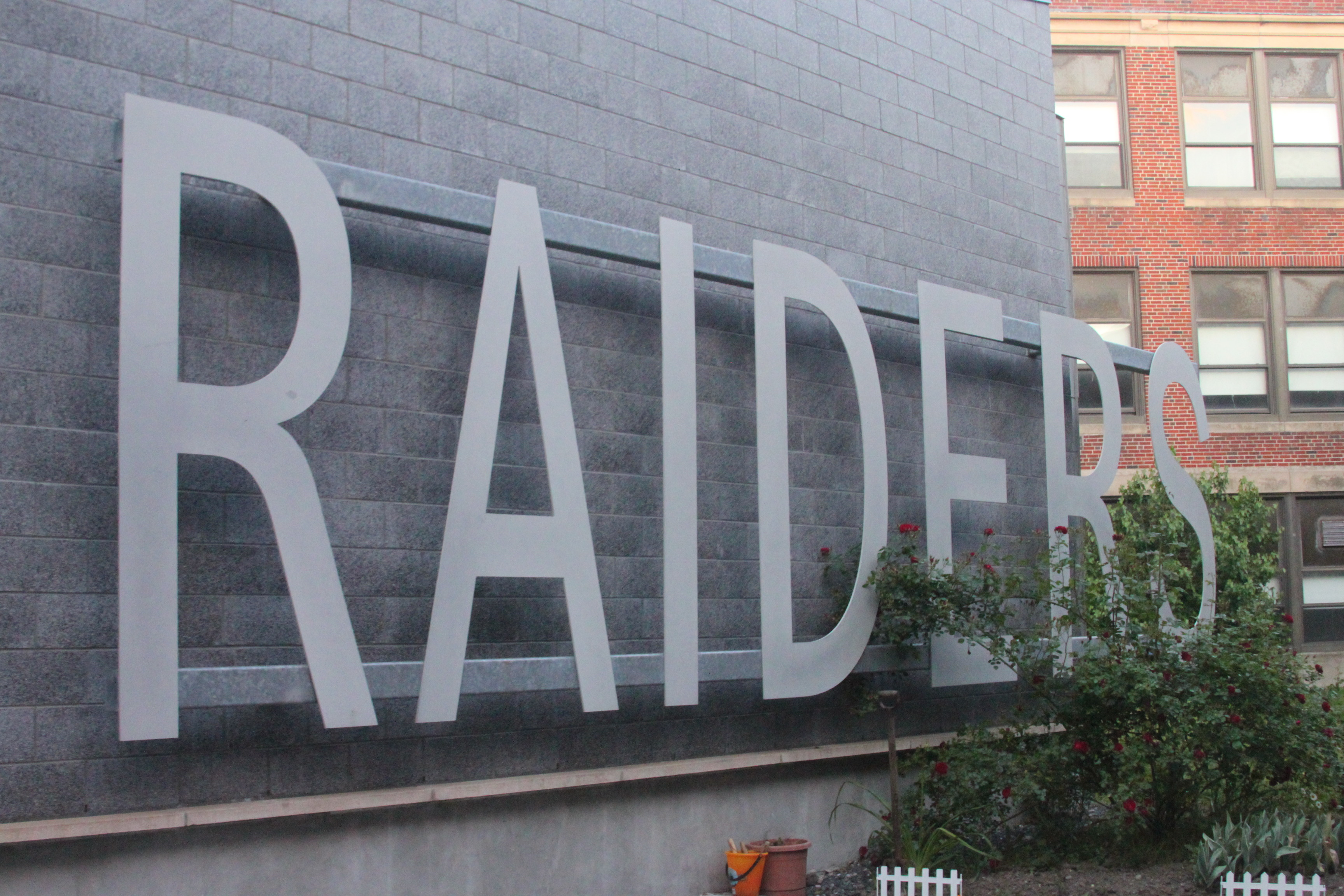 A sign inside an atrium at Watertown High School displaying the current mascot - the Raiders.