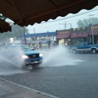 A pickup drives through the rainwater that covered Mt. Auburn Street in Coolidge Square up to the curb  on Monday.