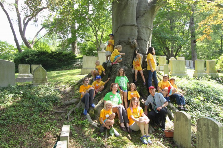 Campers from the Church of the Good Shepherd's Vacation Garden Camp sit on the roots of a tree at Mount Auburn Cemetery.
