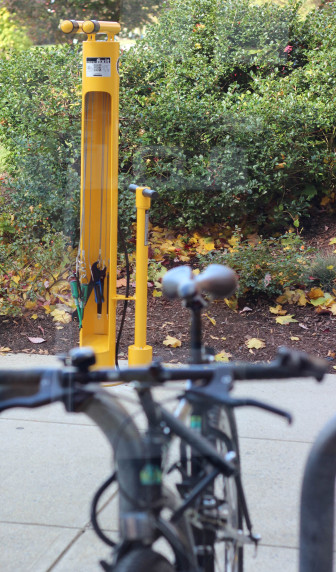 The new bicycle repair station is in front of the library near the bike racks.