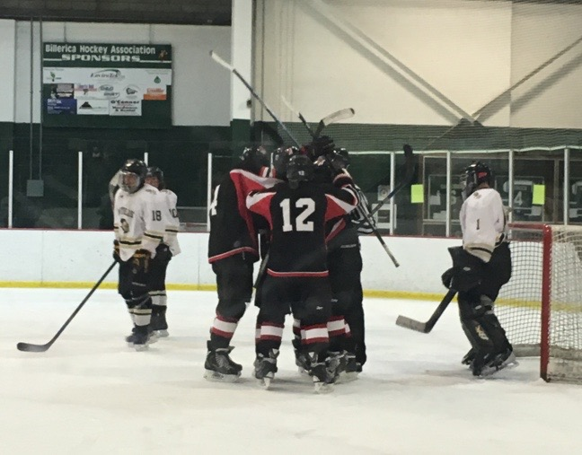 The Watertown hockey team celebrates scoring against Northeast Regional in the state tournament.