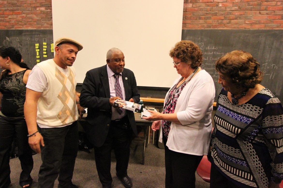 "Civil Rights leader Dr. Bernard Lafayette presents Watertown Superintendent Jean Fitzgerald with a book during the celebration of the end of the Kingian Nonviolence training. With them are Lafayette's wife, Kate, (right) and Nonviolence trainer Jonathan ""Globe"" Lewis, left."
