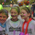 Three girls covered in color powder after the Crazy Color Race.