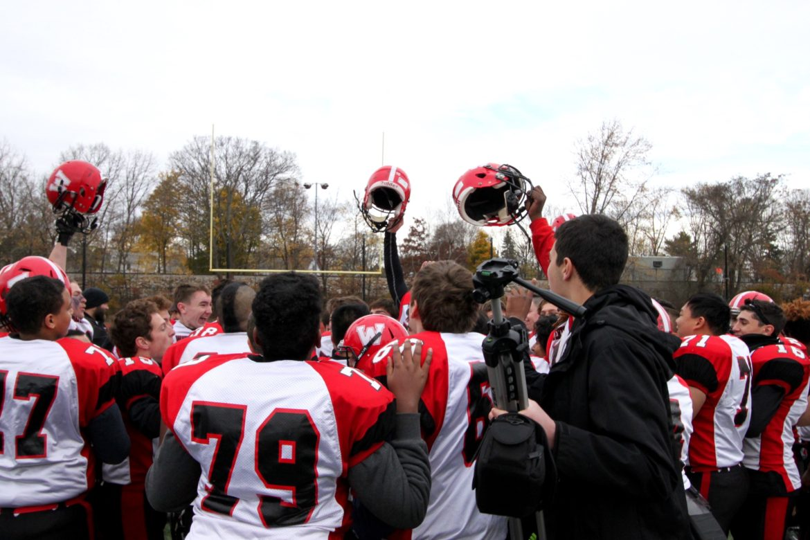 The Raiders celebrate after learning they had won the Middlesex League Freedom Division title following the Thanksgiving Day game.